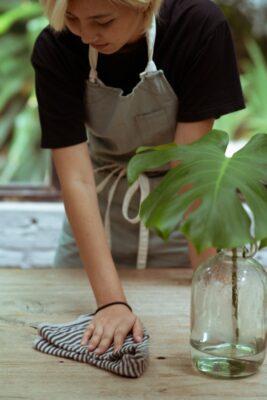 kobieta w fartuchu ściarająca kurze z blatu stołu
