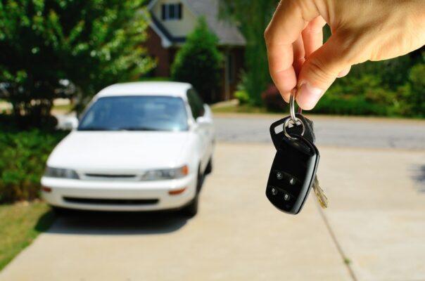 kluczyki do samochodu w dłoni - w tle samochód stojący na podjeździe