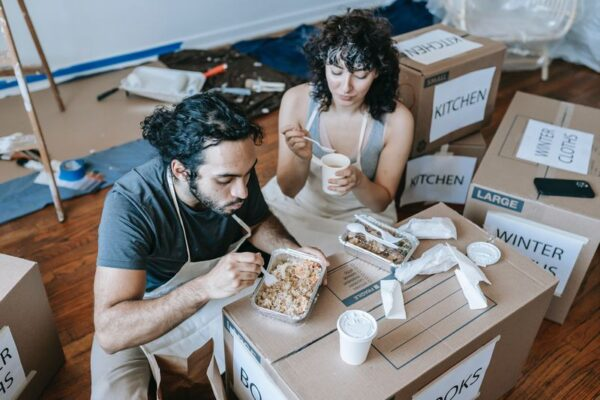 kobieta i mężczyzna jedzą posiłek na kartonach - opakowania ekologiczne